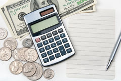 Calculator, empty lined paper, money and pen Stock Image