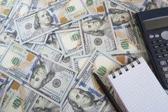Calculator en dloknot tegen de achtergrond van Amerikaanse dollars Stock Afbeeldingen