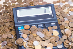 Calculator en een stapel muntstukken Stock Foto's