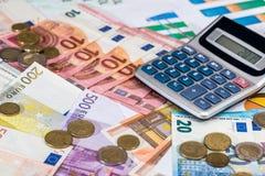 Calculator en euro muntstuk die op euro liggen Stock Afbeelding