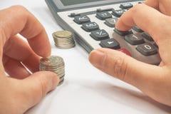 Calculator en het stapelen van muntstukken in kolommen stock fotografie
