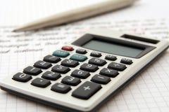 Calculator en pen die op het werk/studie wijzen royalty-vrije stock afbeeldingen