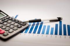 Calculator en pen en grafiekenanalyse Stock Foto