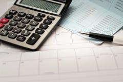 Calculator en pen en kalenderachtergrond Royalty-vrije Stock Foto
