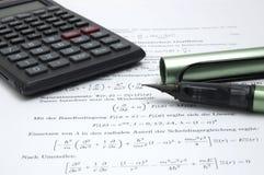 Calculator en pen op wetenschappelijk document stock fotografie