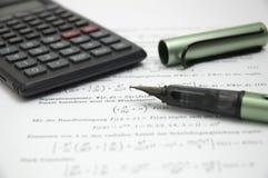 Calculator en pen op wetenschappelijk document royalty-vrije stock afbeeldingen