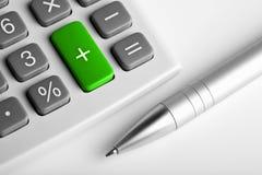 Calculator en pen. plus groene gekleurd knoop Stock Fotografie