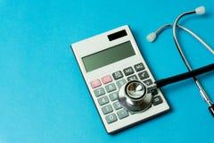 Calculator en stethoscoop op blauwe achtergrond Stock Foto's