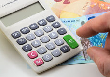 Calculator with euro notes on background. Green Key with Euro sign. Stock Photos