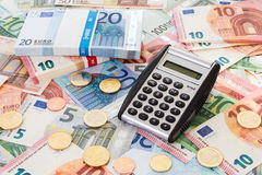 Calculator with Euro notes and coins Stock Images