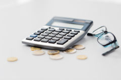 Calculator, eyeglasses and coins on office table Royalty Free Stock Images