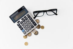 Calculator, eyeglasses and euro coins on table Royalty Free Stock Photography