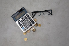 Calculator, eyeglasses and euro coins on table Stock Photography