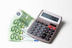 Calculator with fanned Euro notes and coins on white background Stock Image