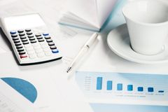Calculator with financial charts on a table with coffe cup stock photos