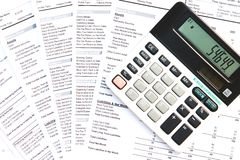 Calculator and financial documents. Calculator on top of financial documents royalty free stock image
