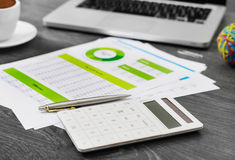 Calculator and financial papers. Financial data on papers and calculator Stock Photography