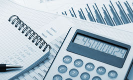 The calculator and the financial report blue toned stock photos