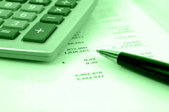 Calculator on financial statement. With green overlay and shallow DOF royalty free stock images
