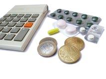 Calculator, geneesmiddelen en euro geïsoleerde geldmuntstukken Royalty-vrije Stock Foto