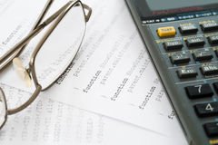 Calculator and glass place on code Stock Photography