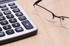 Calculator and glasses. Clculator and glasses on the wood table Royalty Free Stock Photography
