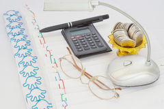 Calculator with glasses and coins in gold tray with pedestal Royalty Free Stock Photo