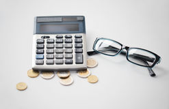 Calculator, glasses and euro coins on office table Stock Photos