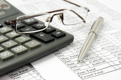 Calculator and glasses on financial report Royalty Free Stock Images