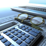 Calculator, Glasses and Laptop. A calculator, ball point pen, round reading glasses and a laptop computer on top of a paper financial report Royalty Free Stock Photos