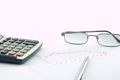 Calculator, glasses, pen and graph Stock Photo