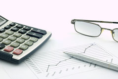 Calculator, glasses, pen and pos. graph Royalty Free Stock Photography