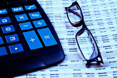 Calculator and glasses on top of financial paper Stock Photos
