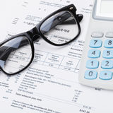 Calculator and glasses with utility bill under it - close up Royalty Free Stock Photography