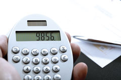 Calculator in hand, bank transfer and ball pen Stock Photography