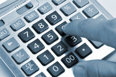 The calculator and a hand of the man Stock Images