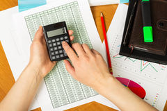 Calculator in hand of the woman, notebook on  desktop background Royalty Free Stock Images