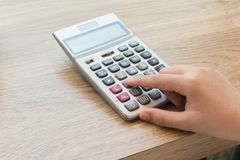 Calculator with hand on wood desk. Calculator with hand on wood desk Stock Image