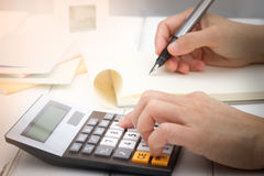 Calculator. Hand writing and counting on calculator in office on wood desk about financial data analyzing, Choose focus point Stock Image