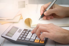 Calculator. Hand writing and counting on calculator in office on wood desk about financial data analyzing, Choose focus point Royalty Free Stock Photography