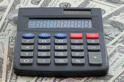 Calculator on heap of money Stock Images