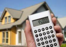 Modern house and calculator. Calculator with a high sum in front of a modern family house royalty free stock images