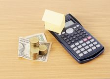 Calculator and home paper and Dollar money with coins stack on W. Ooden desk for Loans concept stock photography