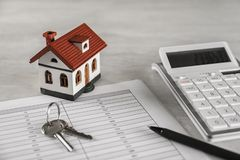 Calculator, house model, keys and documents. Real estate agent`s workplace