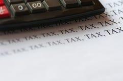 Calculator and increasing tax word. Calculator and increasing tax word, conceptual increasing tax image close up Royalty Free Stock Photo