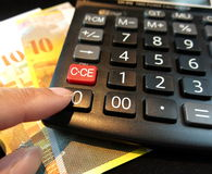 Calculator juxtaposed against swiss franc Royalty Free Stock Images