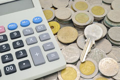 Calculator, key and stack of coins Royalty Free Stock Photography