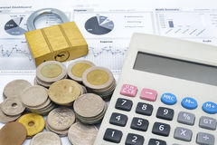Calculator, key and stack of coins on a paper of financial graph Stock Photos