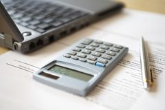 Calculator lying next to laptop close-up Stock Images