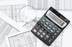 The calculator and magnifier on documents. Royalty Free Stock Photography